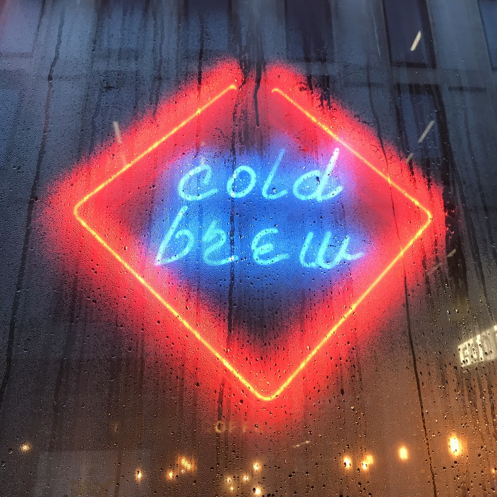 reflection of cold brew neon sign on glass wall