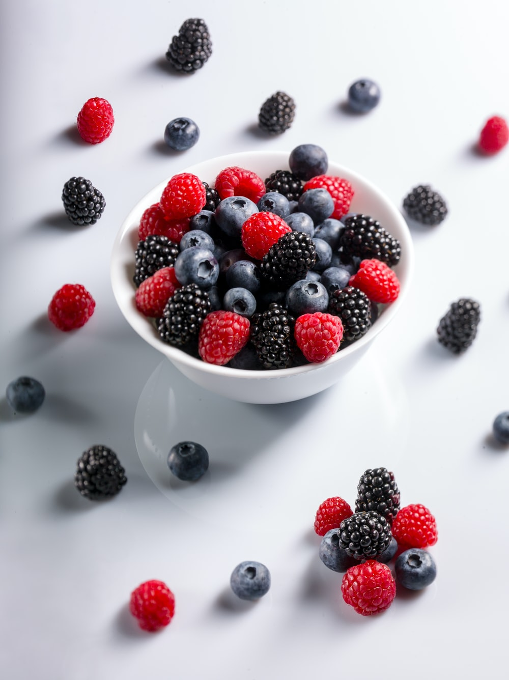 red and black raspberries on bowl