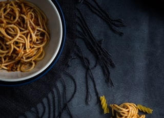 spaghetti on white and blue bowl