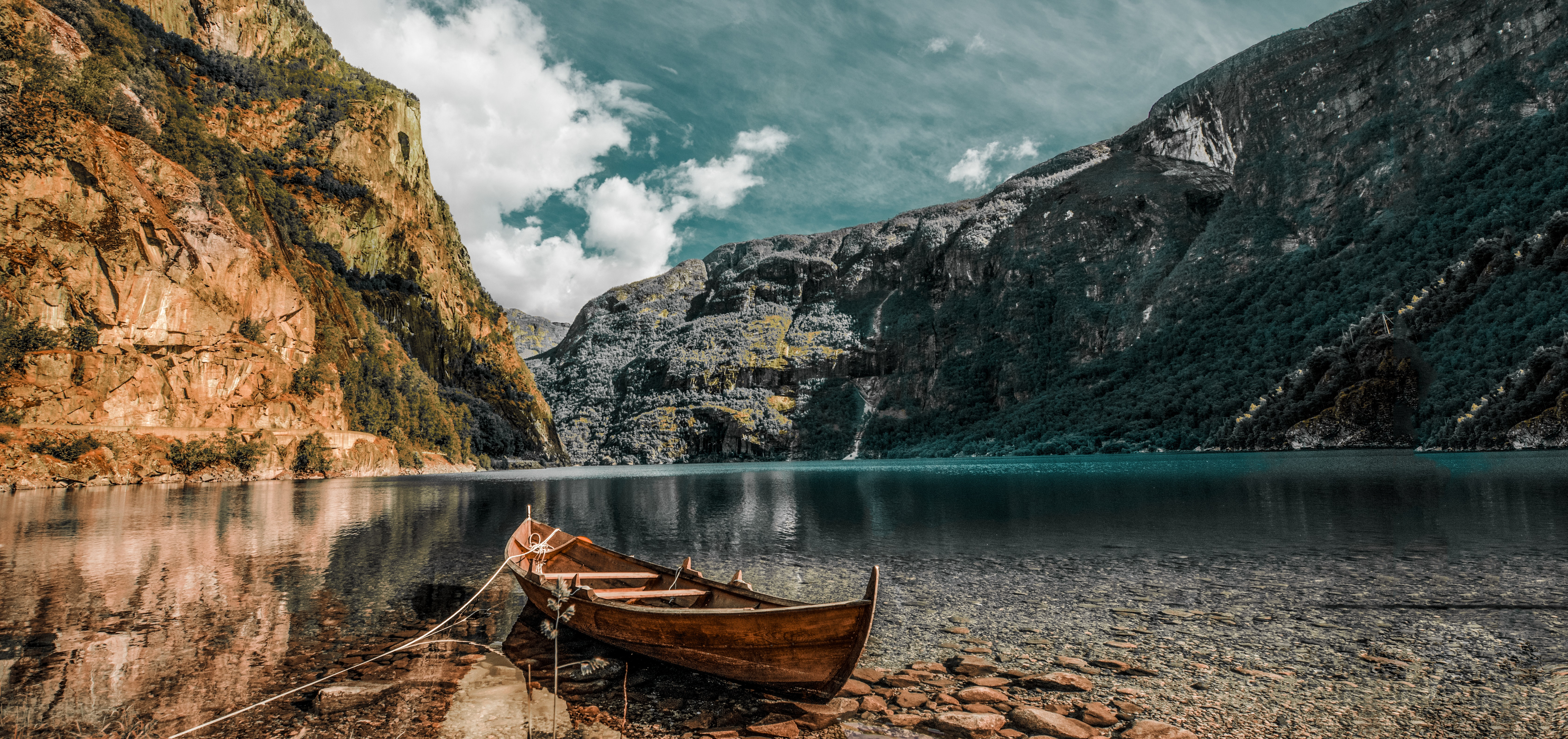 brown wooden canoe next to river and mountains