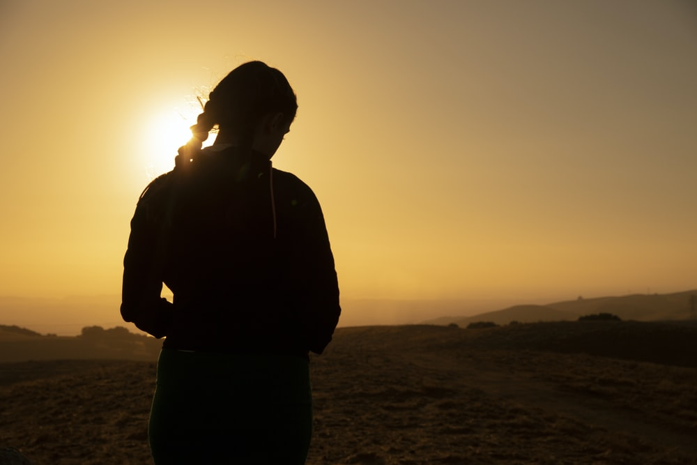 woman standing on vast desert under golden hour