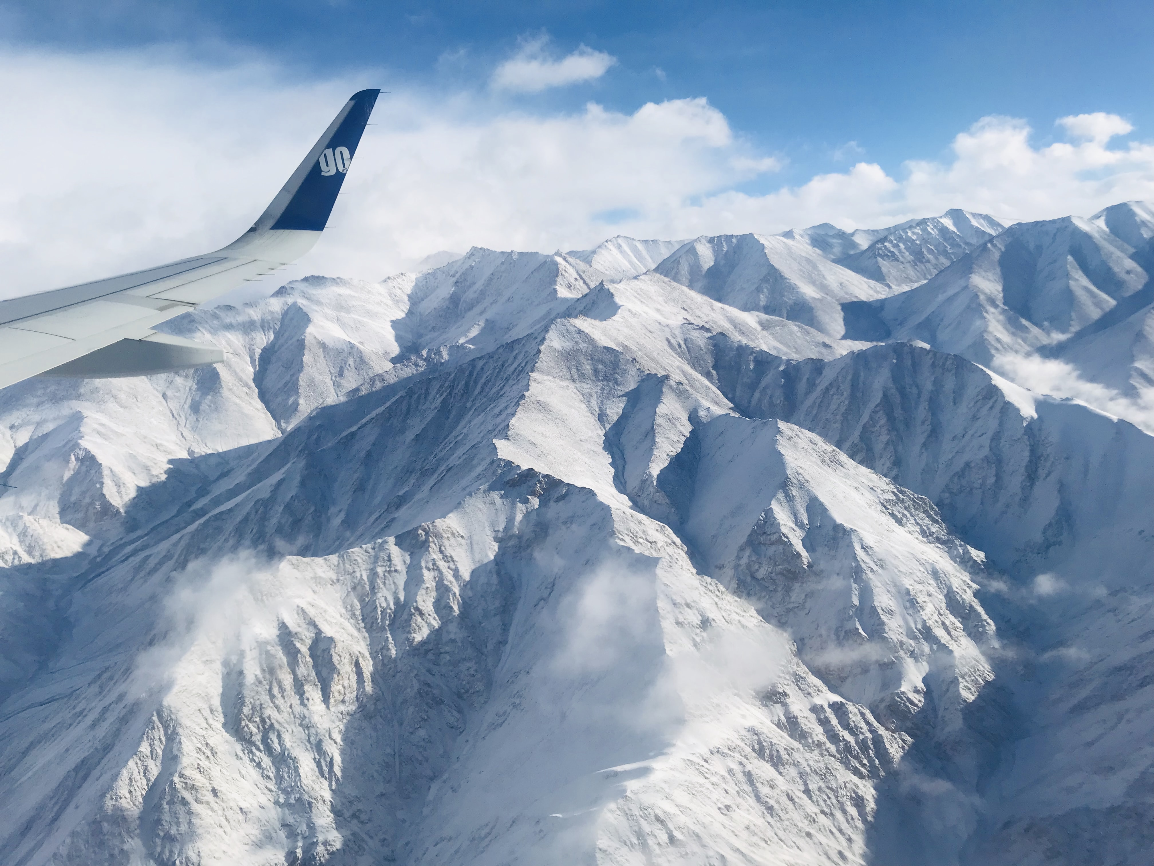 airplane flying near snow covered mountain during daytime