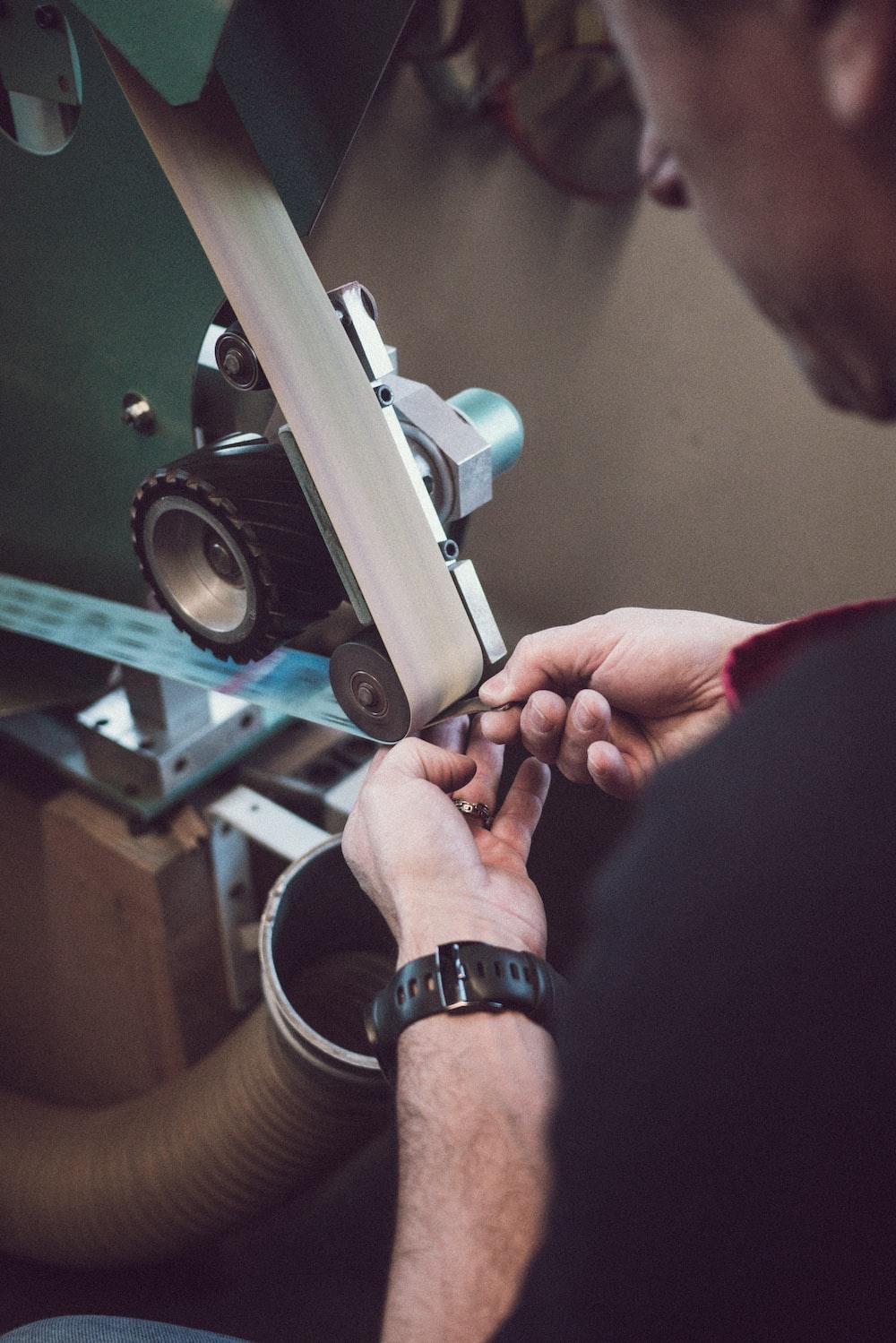 man fixing belt-driven machine