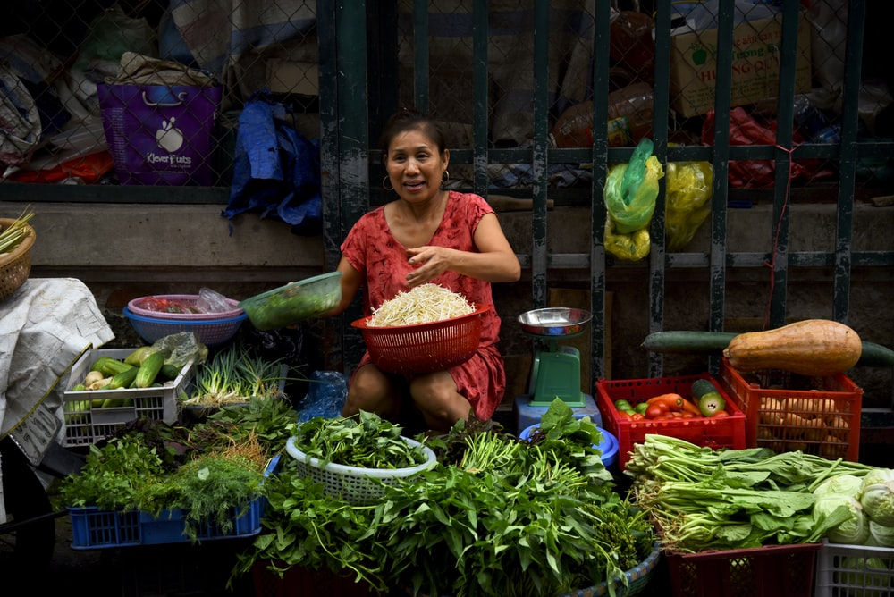 female vendor sits near weighing scale while selling vegetables