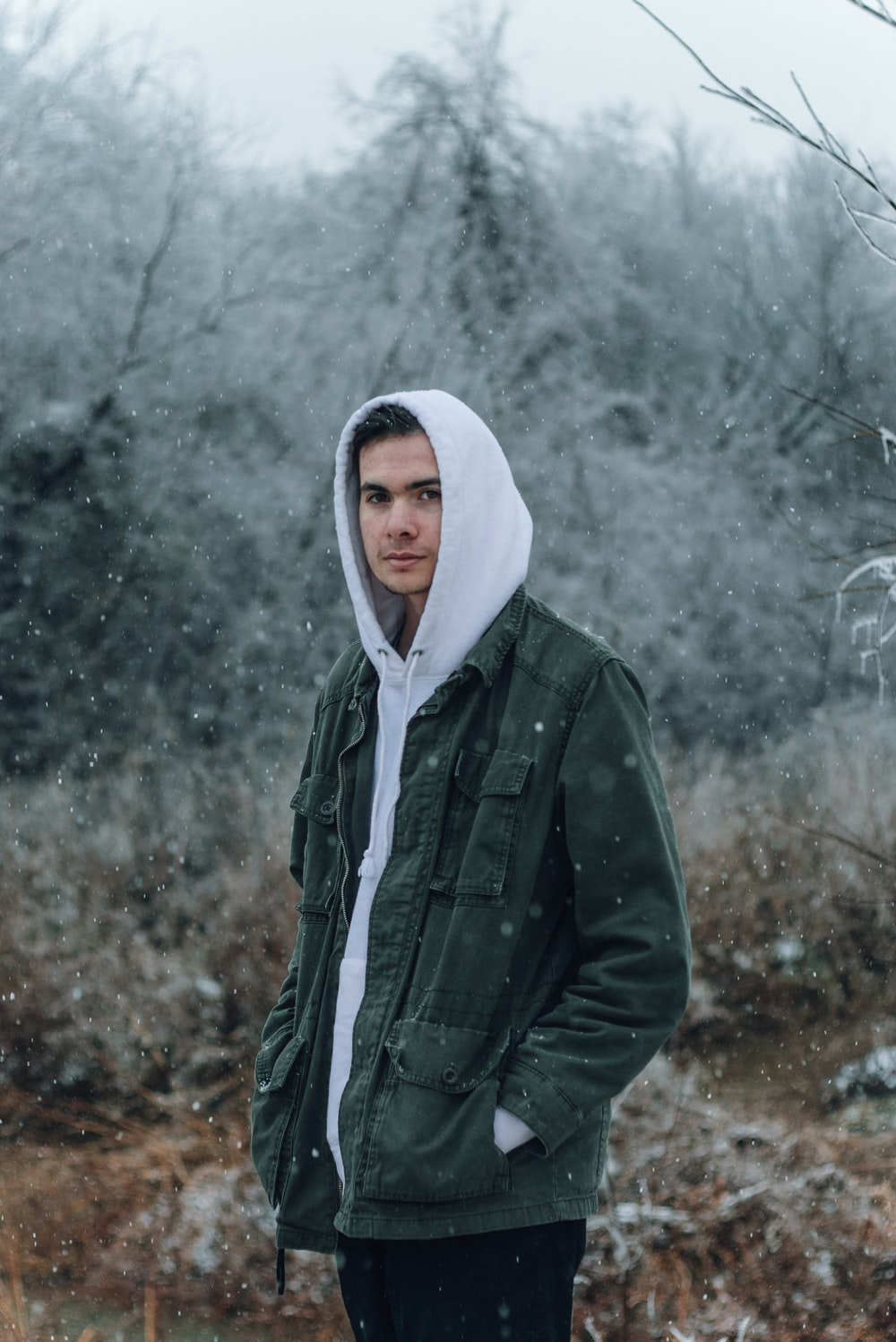 man in grey and green hoodie standing