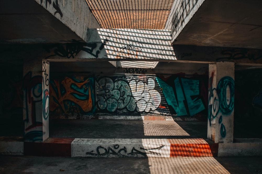 green and multicolored graffiti art on wall