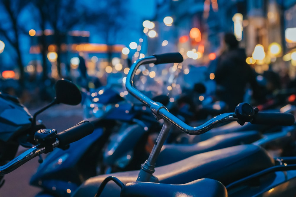 selective focus photography of bike and motorcycle parked outdoors