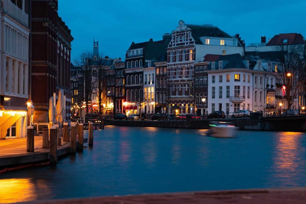 river near buildings at night-time