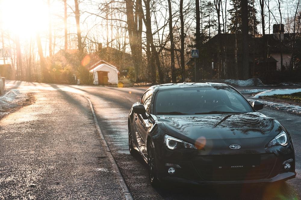 black Subaru vehicle passing on road during daytime