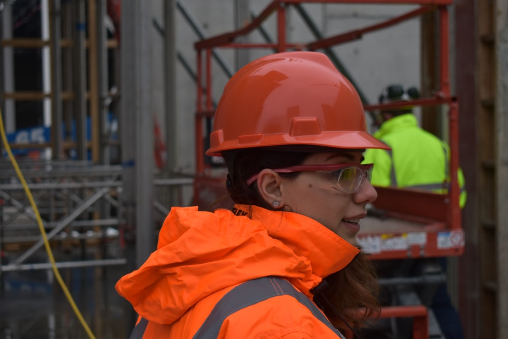woman wearing red hard hat and orange reflectorized jacket