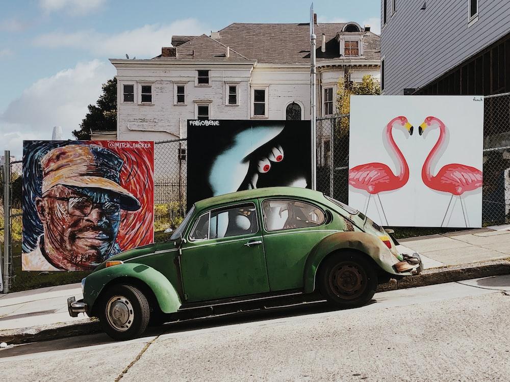 green Volkswagen Beetle parked near wall arts