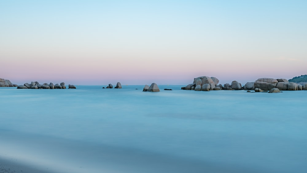rock formation on calm body of water during daytime