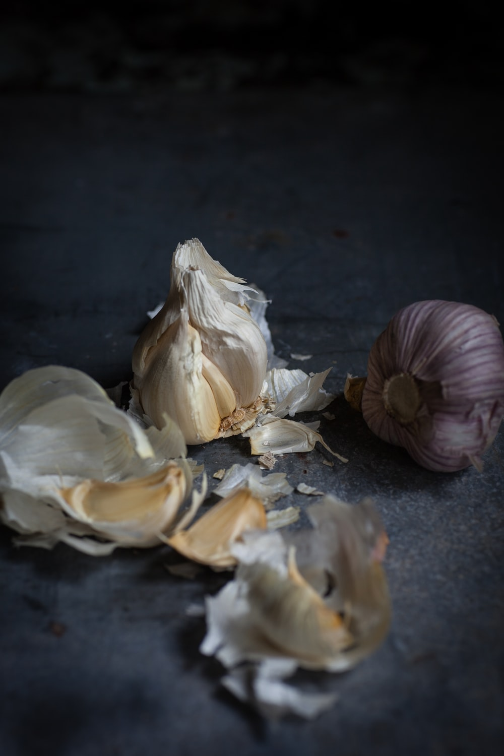 two close-up photography of garlic gloves on gray surface