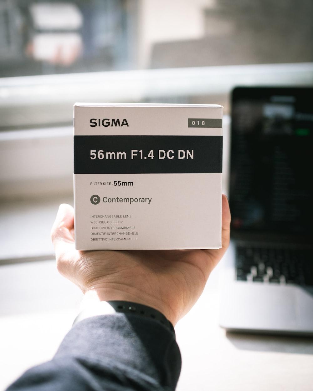 person holding Sigma 55 mm F1.4 DC DN box