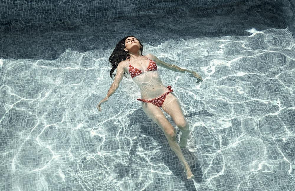 woman wearing red bikini swimming