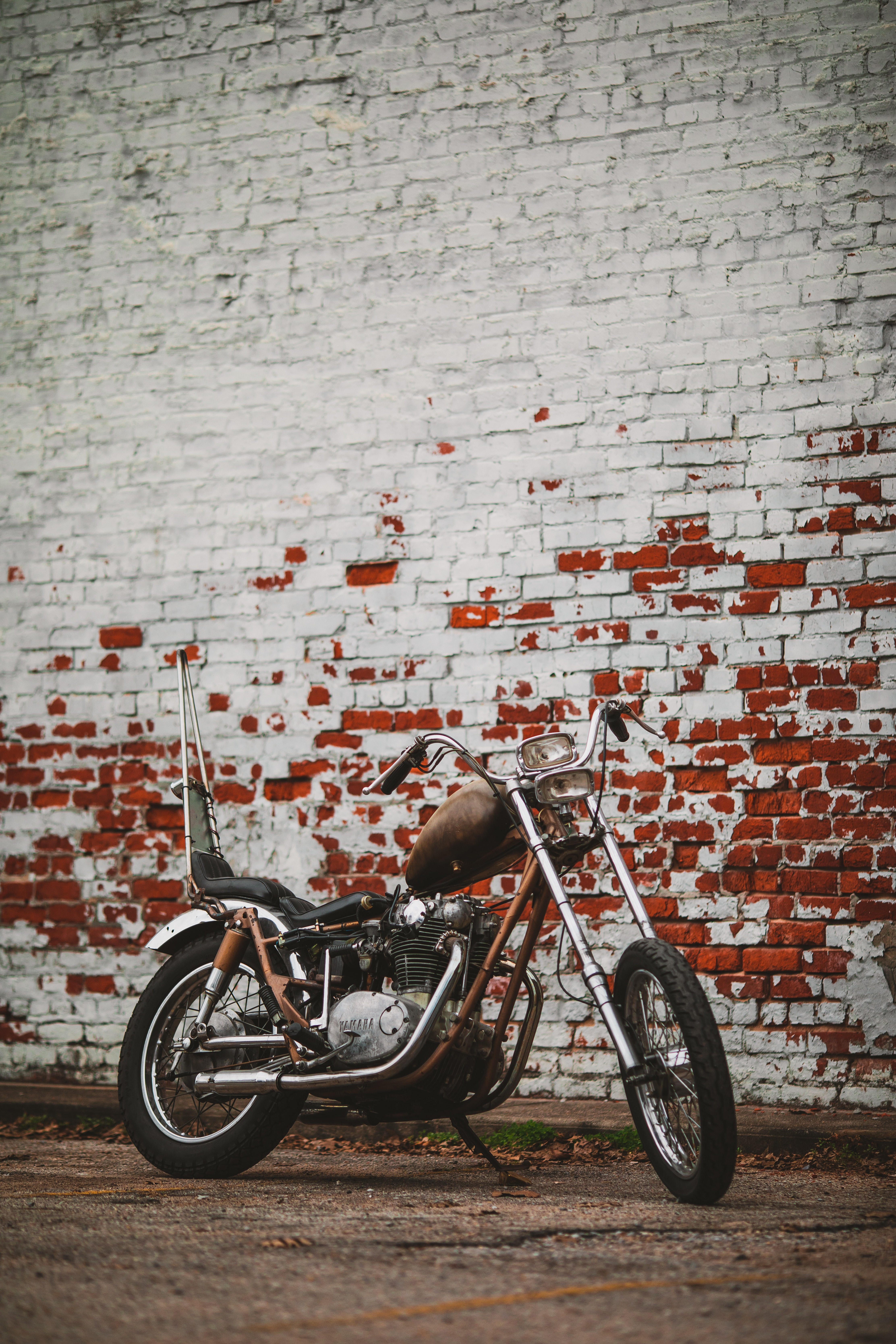 brown and black motorcycle beside brown and red wall