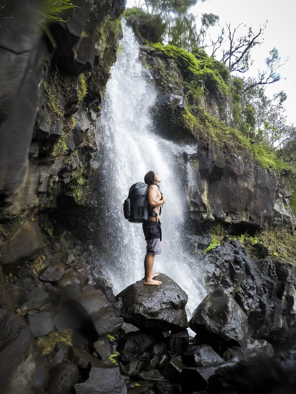 man carrying rucksack backpack standing on stone on front of waterfalls