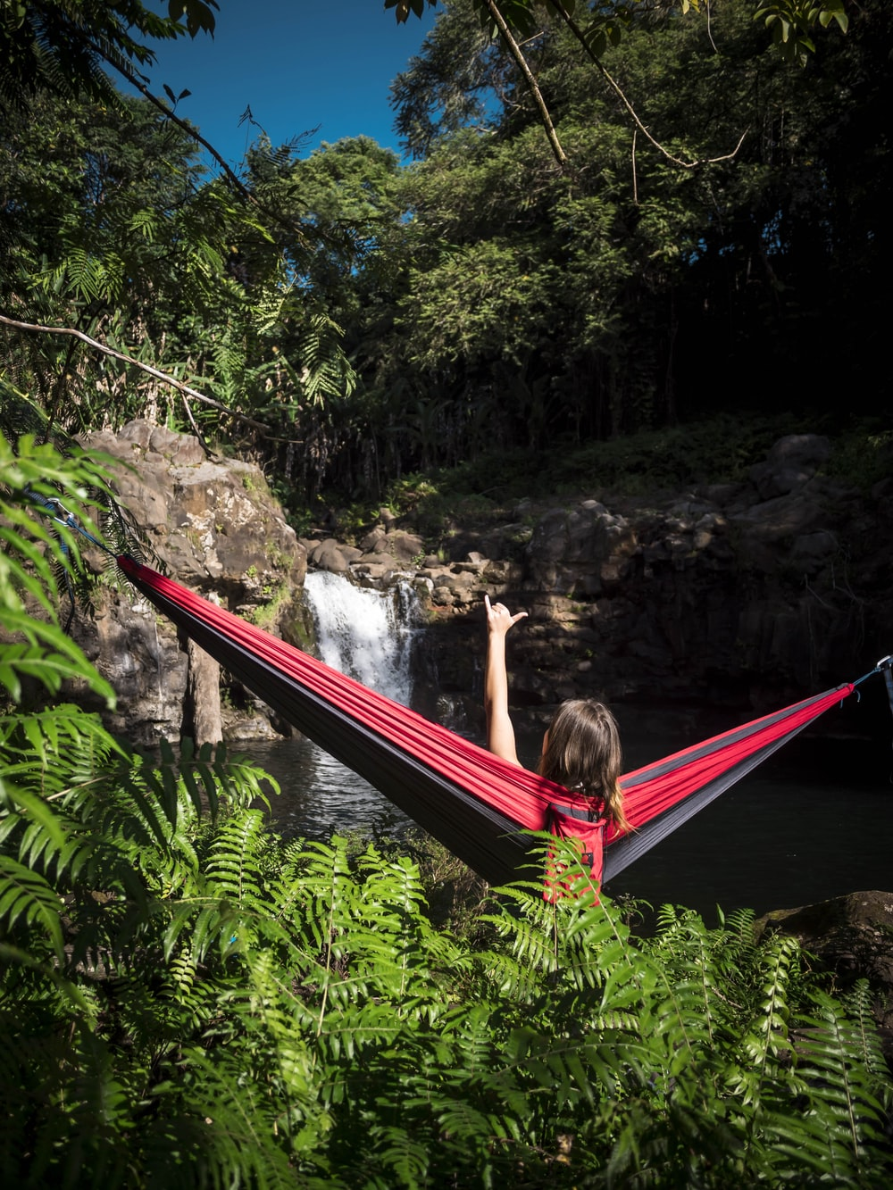 woman sitting on red and black hammock near waterfalls during daytime