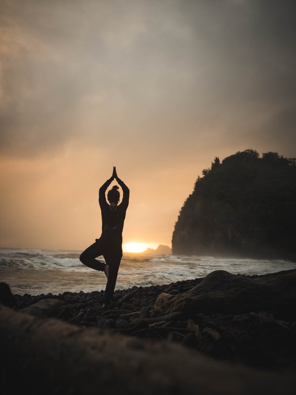 woman doing one-foot yoga stance at the beach under grey sky