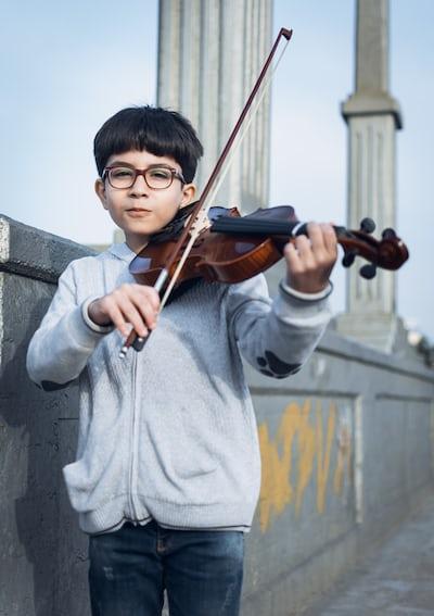 boy in gray zip-up jacket playing violin