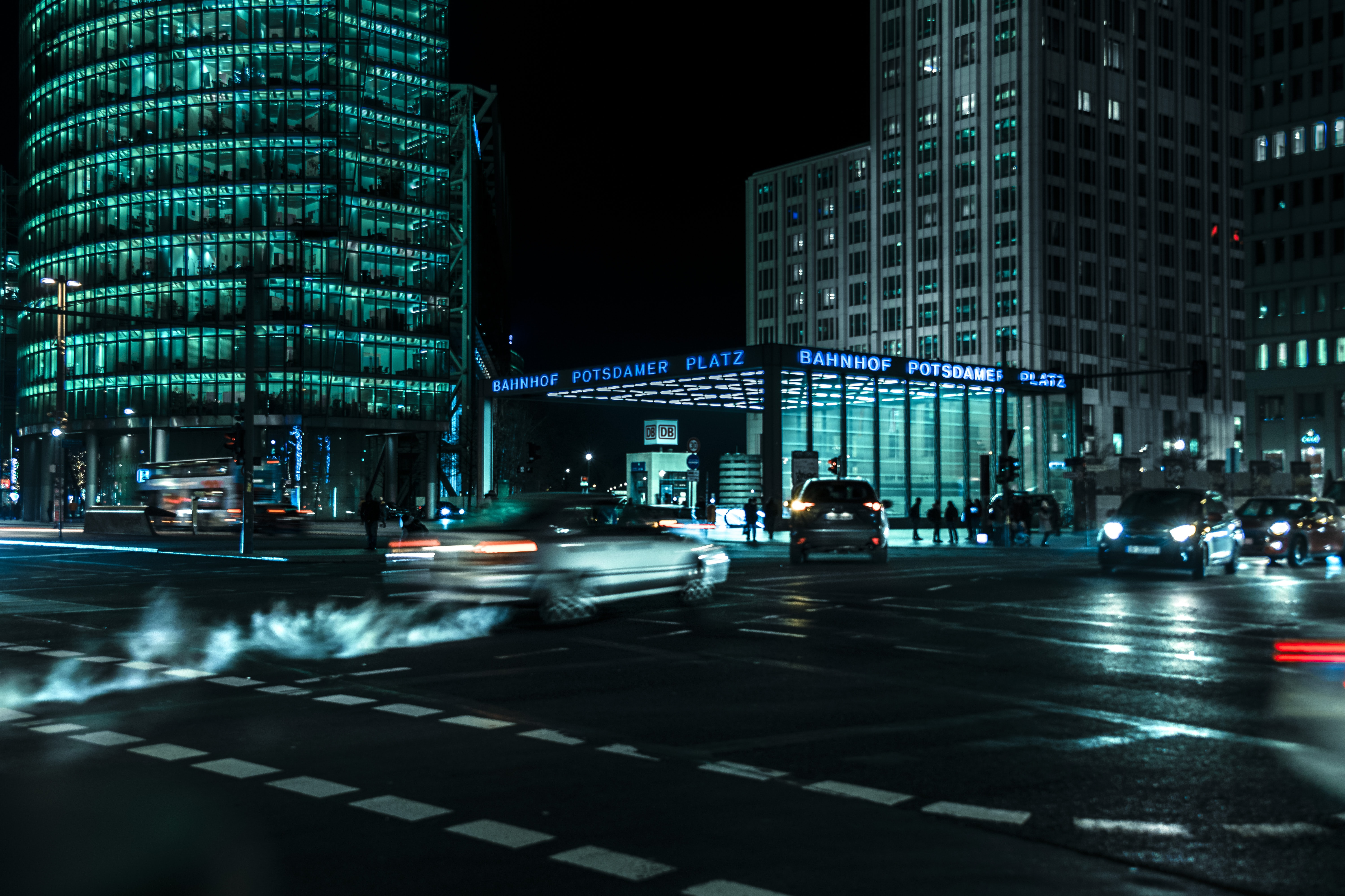 time-lapse photography of vehicles passing on curtain wall high-rise buildings during night