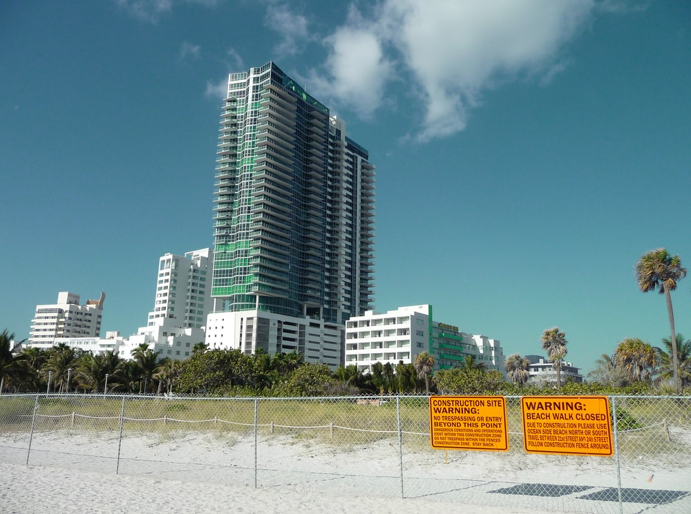 two yellow warning signs on fence near curtain-wall high-rise building