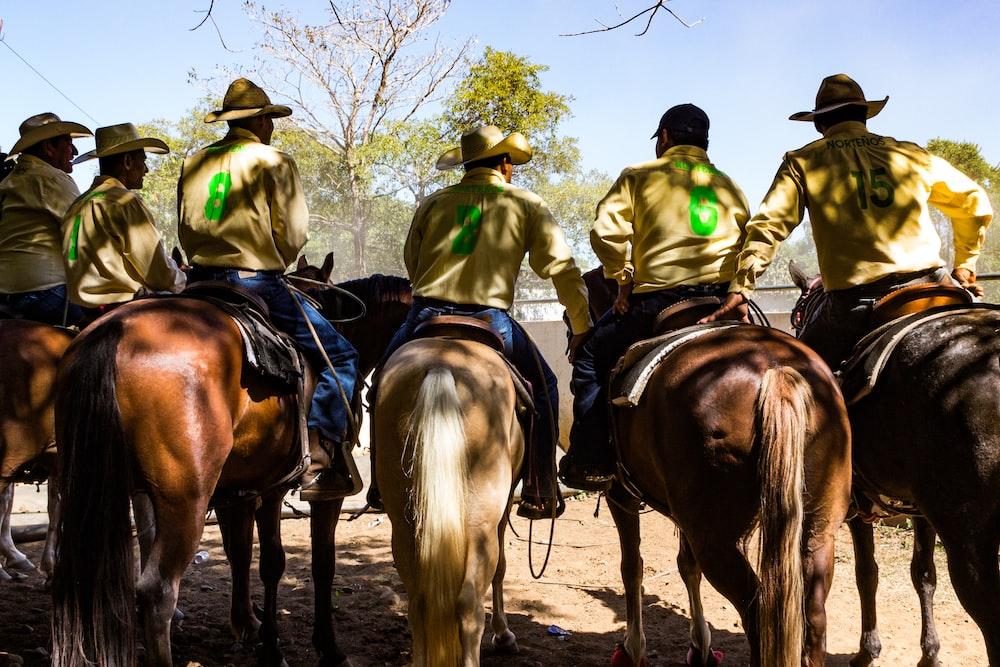 six men riding horse during daytime