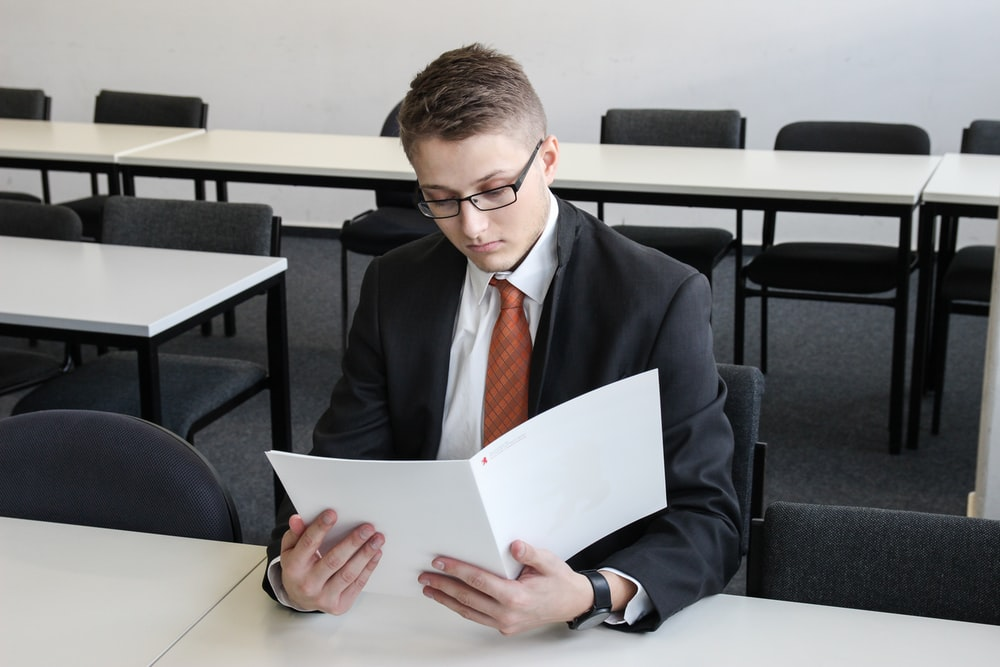 man holding folder in empty room