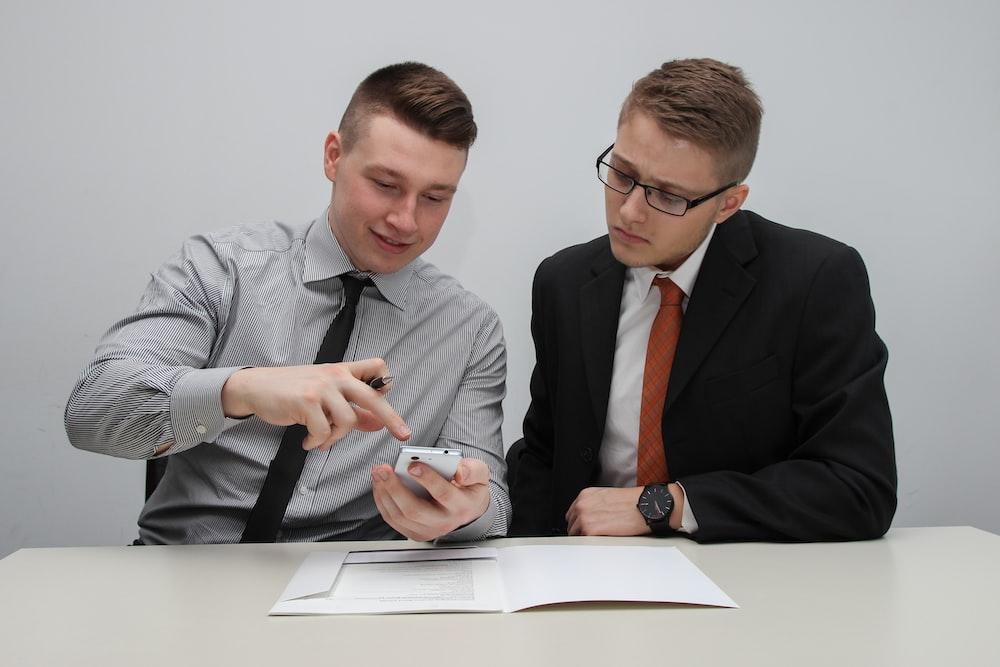 two man watching smartphone