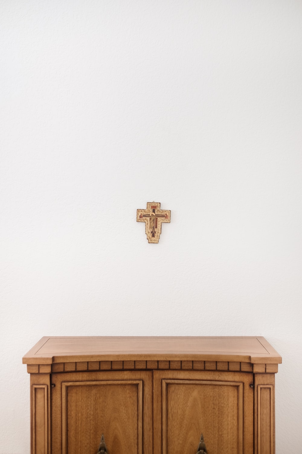 brown cross on wall above brown wooden sideboard