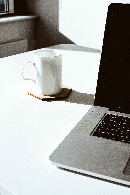 white mug beside MacBook Pro