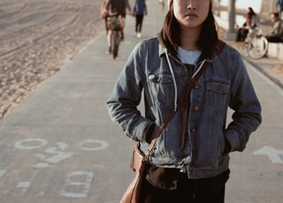 woman standing while putting her two hands on her jacket pocket near person biking during daytime
