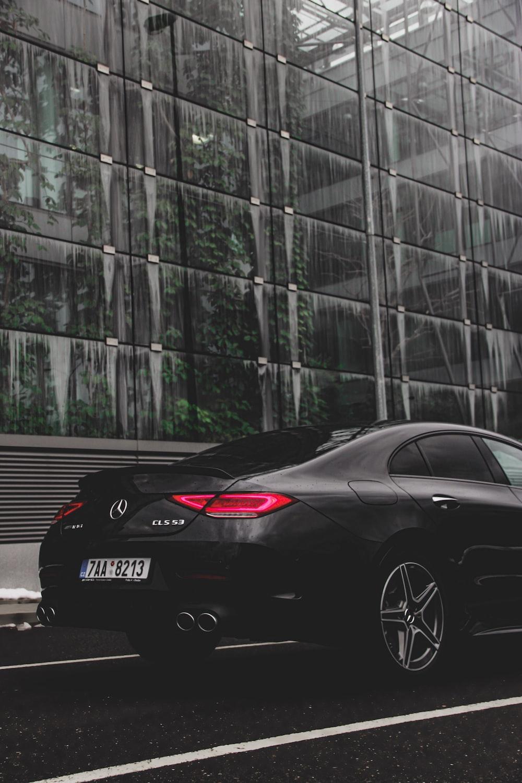black Mercedes-Benz park near greenhouse