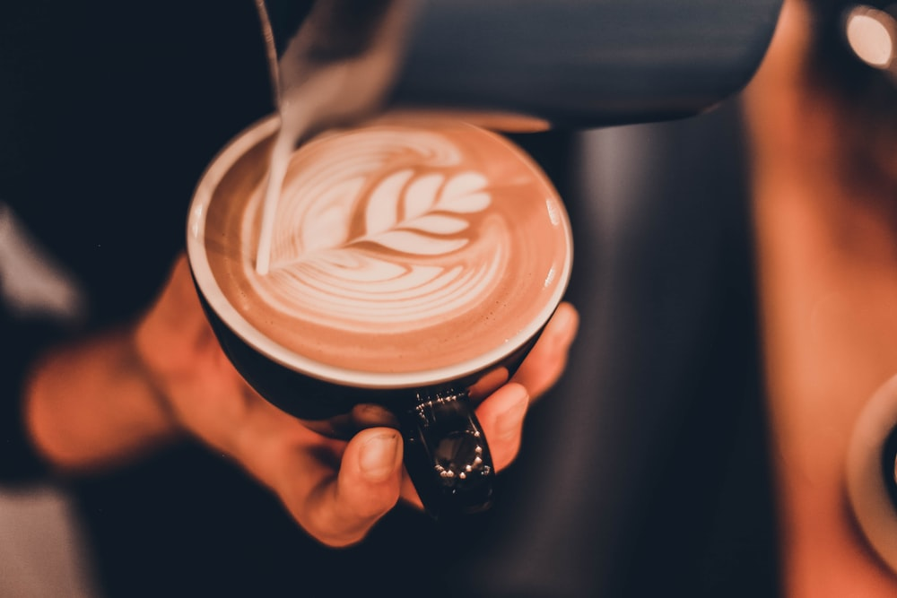 person pouring milk on coffee
