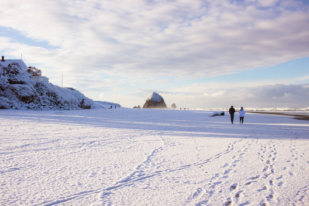 two persons walking on snow field during daytime