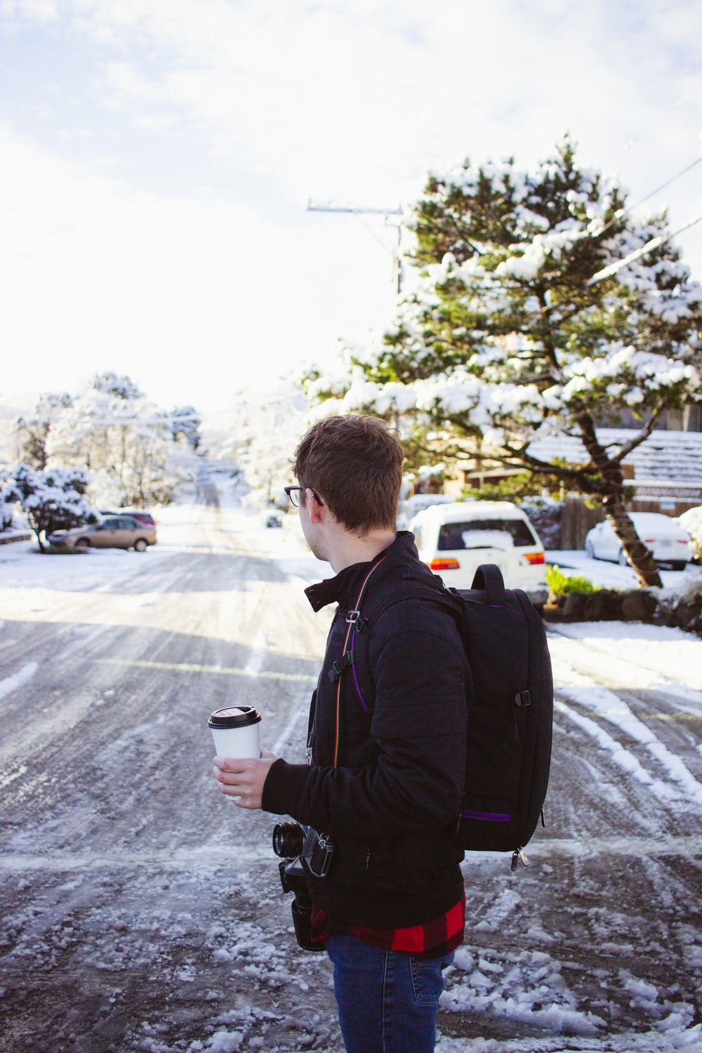 man holding cup of coffee wearing backpack leaning on vehicle during daytime