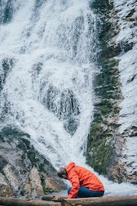 man in red hoodie sitting on log beside waterfalls