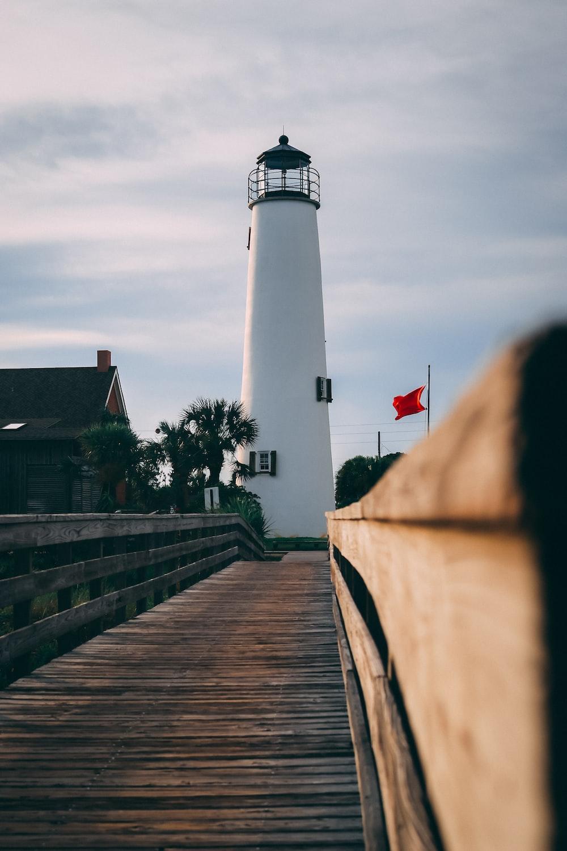 brown wooden bridge near white lighthouse