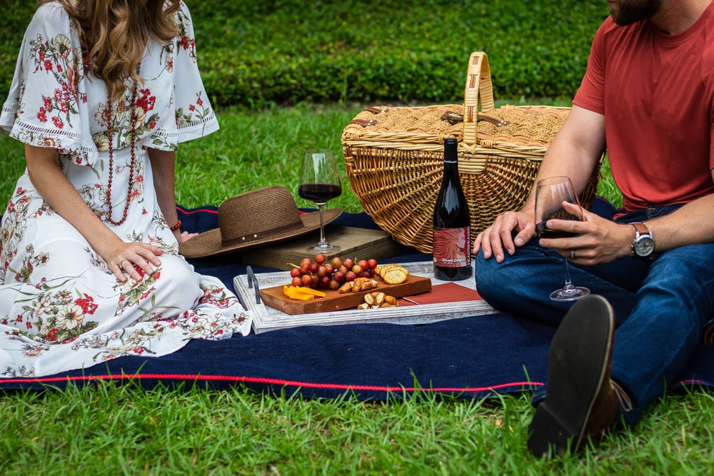 man and woman sitting on blue textile beside brown wicker picnic basket