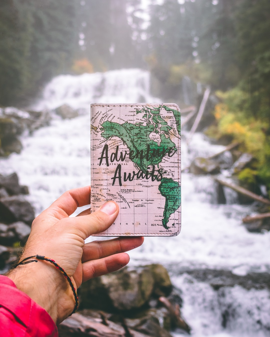 A photo session at a waterfall. Passport holder from https://thewanderlabs.com