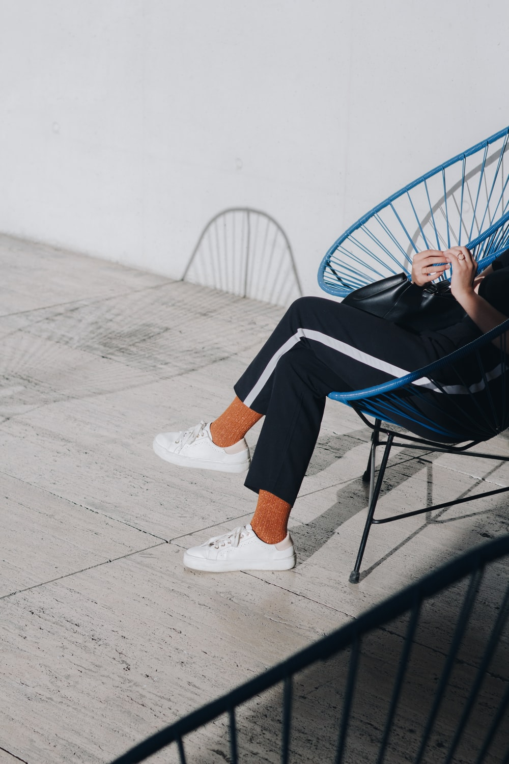 person in black pants sitting chair