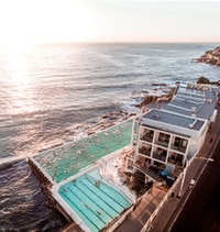 house with swimming pool beside sea during daytime