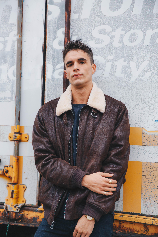 man wearing brown leather zip-up jacket