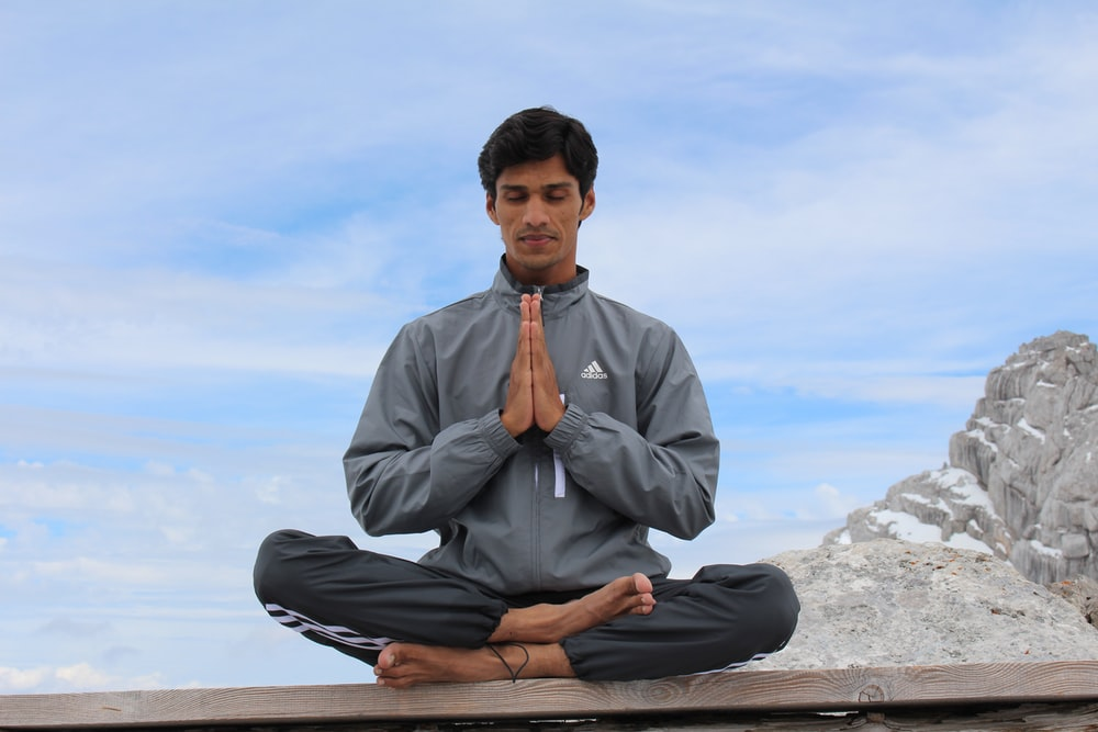 man meditating on brown wooden platform during daytime