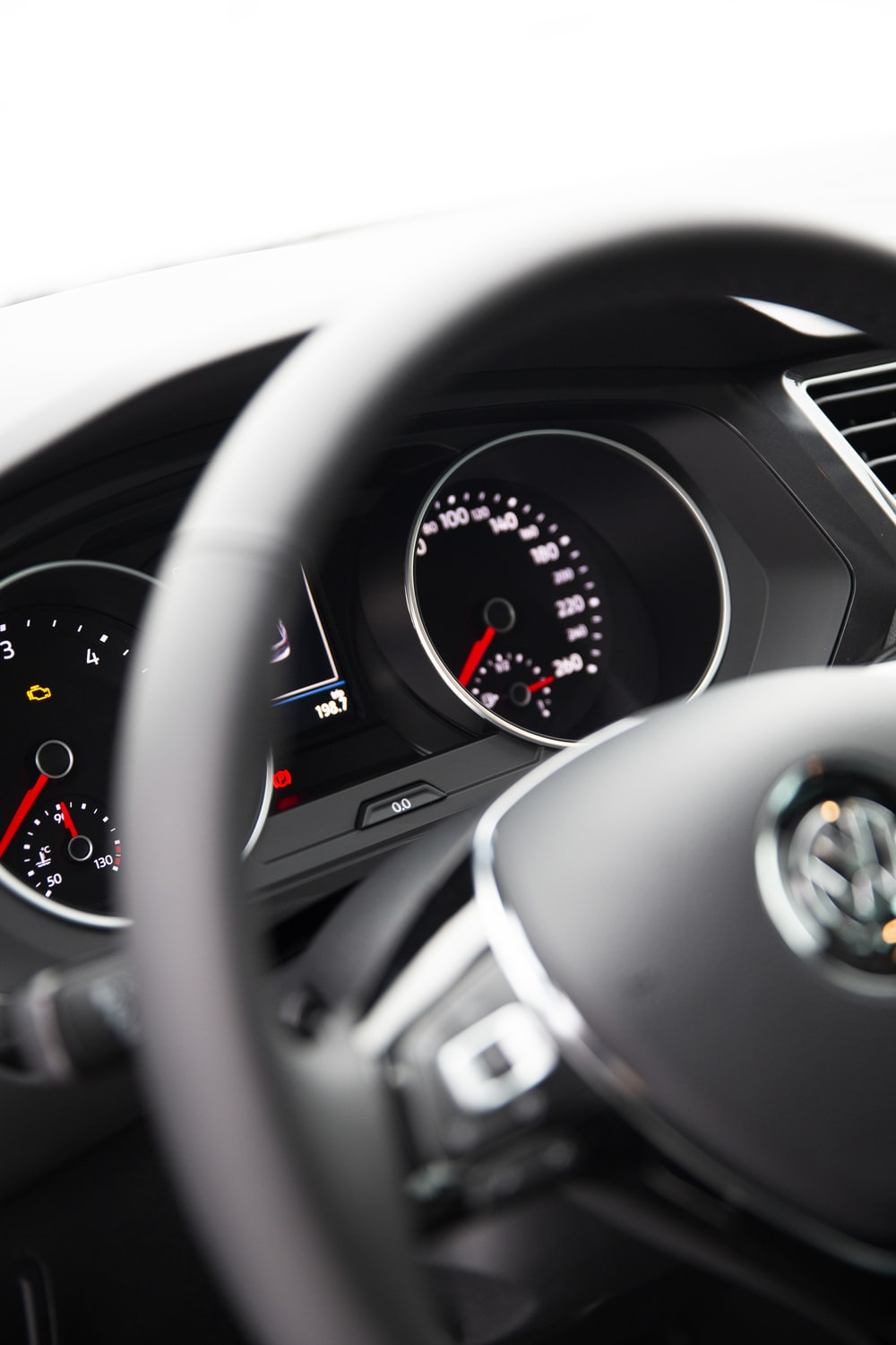 selective focus photography of vehicle analog speedometer control panel