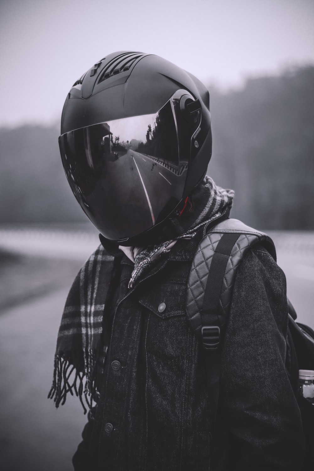 person wearing helmet and backpack in grayscale photo