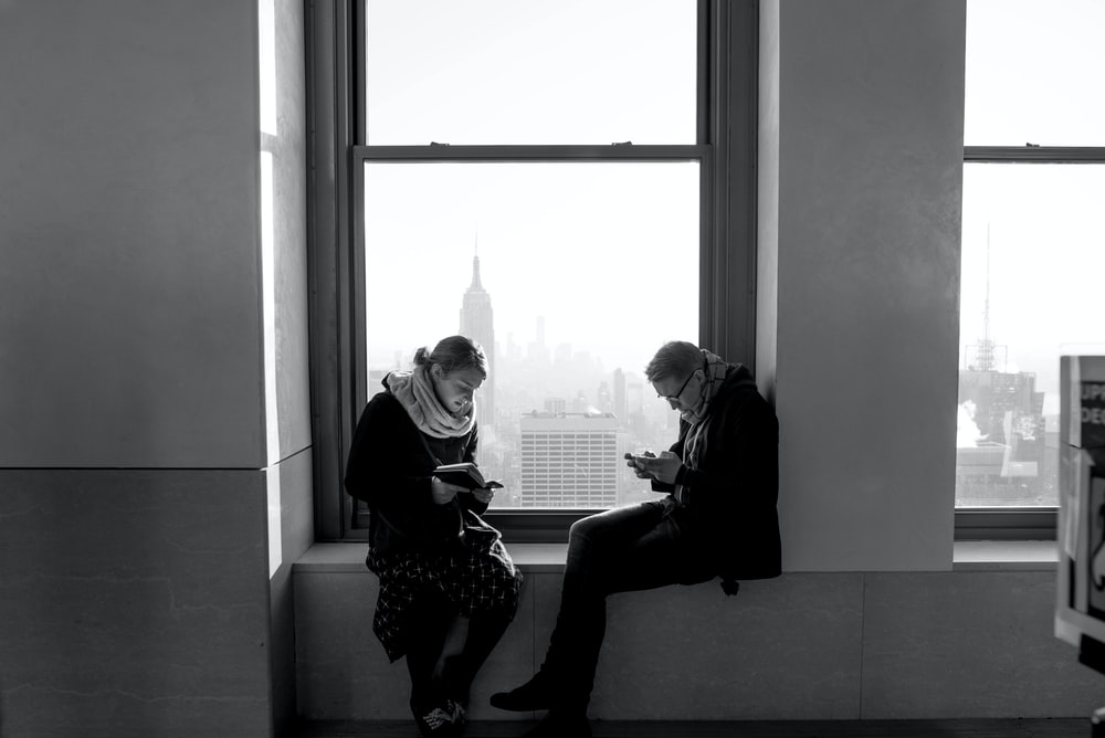 man and woman sitting near window inside building