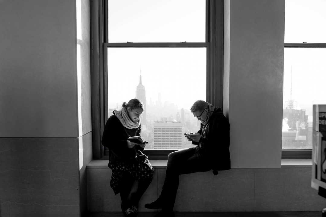 Two strangers at the observatory on top of the Rockefeller Center at New York city. A magnificent view, but they're both preoccupied with their own entertainment.