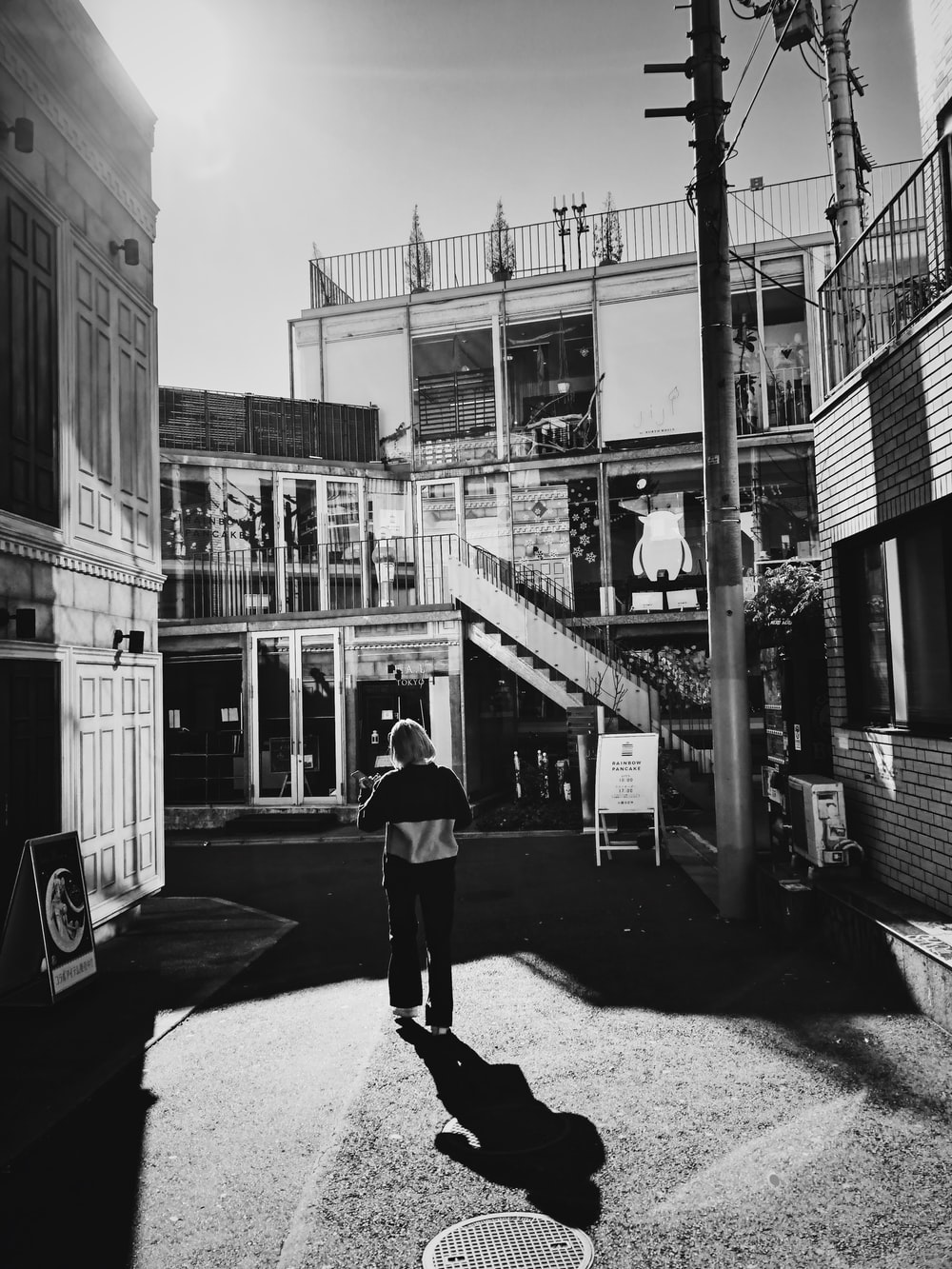 person standing in front of building in greyscale photographt