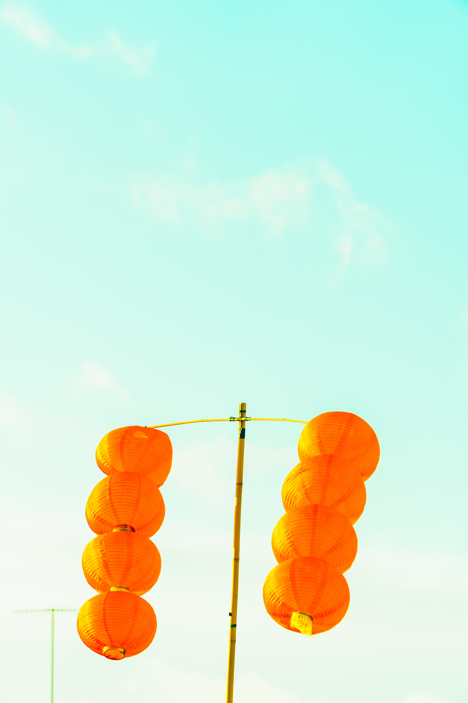 orange hanging lantern under blue sky